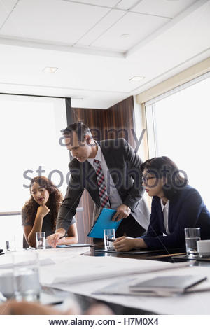 Architects reviewing blueprints in conference room meeting - Stock Photo