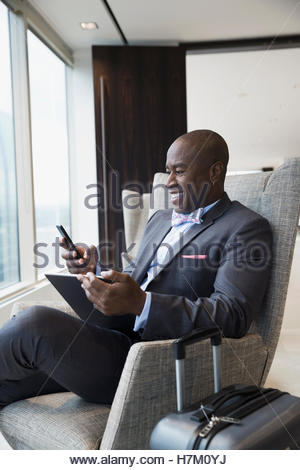 Smiling businessman with luggage using cell phone and digital tablet in airport lounge - Stock Photo