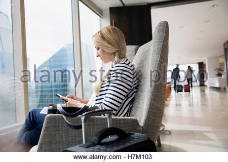 Businesswoman with luggage texting at window in airport lounge - Stock Photo