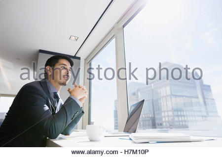 Pensive businessman at laptop looking out urban office window - Stock Photo