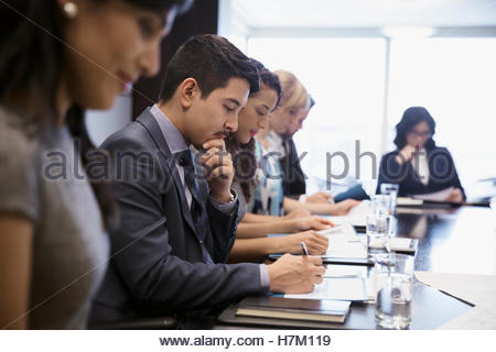 Business people reviewing paperwork in conference room meeting - Stock Photo