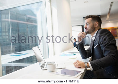 Pensive businessman working at laptop looking out urban office window - Stock Photo