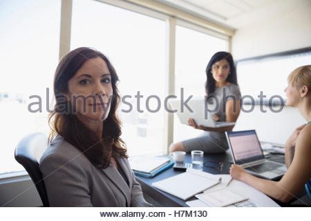 Portrait confident businesswoman in conference room meeting - Stock Photo