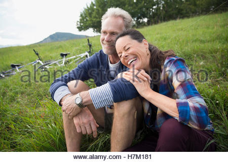 Laughing senior couple relaxing near mountain bikes in remote rural field - Stock Photo