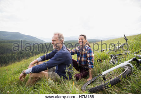 Portrait smiling senior couple relaxing near mountain bikes in remote rural field - Stock Photo