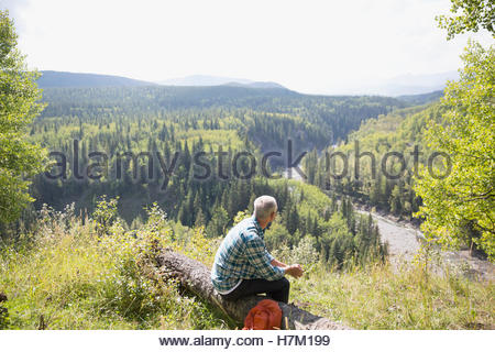 Mature man hiking resting on log at sunny remote rural hilltop - Stock Photo
