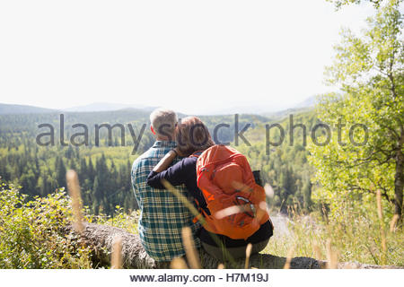 Mature couple with backpack hiking looking at remote sunny rural view from hilltop - Stock Photo