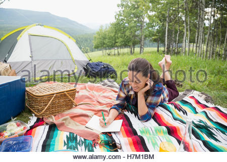 Senior woman writing in journal on blanket at campsite - Stock Photo