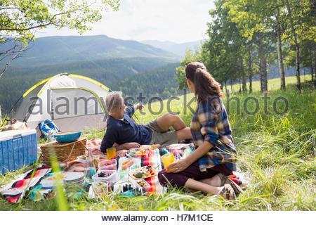 Senior couple enjoying picnic on blanket at campsite - Stock Photo