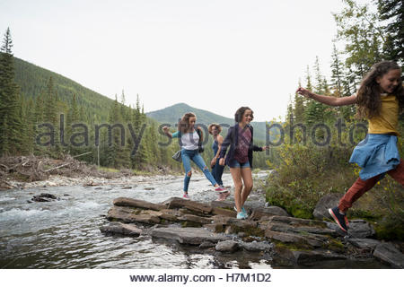 Mother and daughters hiking on rocks along creek - Stock Photo