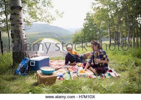 Senior couple enjoying picnic on blanket at rural campsite - Stock Photo