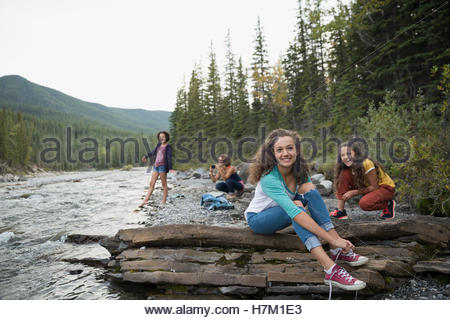 Portrait smiling sisters on rocks along creek - Stock Photo