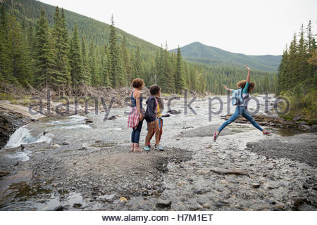 Mother and daughters hiking jumping across craggy creek - Stock Photo