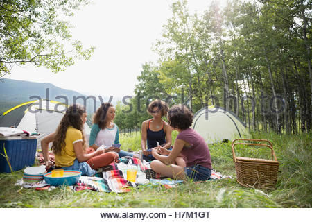 Mother and daughters playing card game on blanket at rural campsite - Stock Photo
