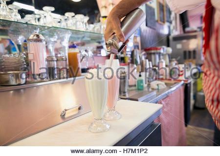 Worker spraying whipped cream on milkshakes in soda fountain shop - Stock Photo