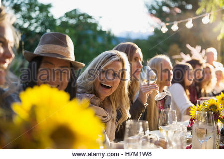 Friends laughing and drinking wine at harvest dinner party - Stock Photo