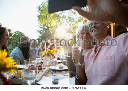 Couple drinking champagne and taking selfie at outdoor harvest dinner party - Stock Photo
