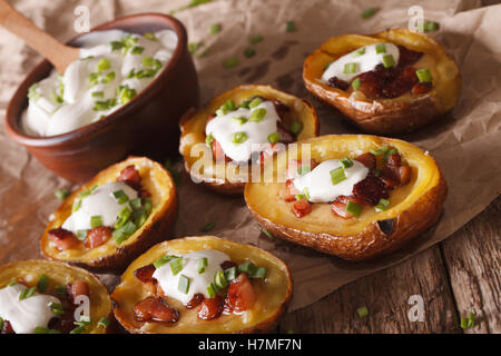 Baked potato skins with cheese, bacon and sour cream close-up on the table. Horizontal - Stock Photo