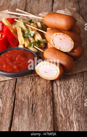 Corn dogs, french fries and ketchup on the table. vertical, rustic - Stock Photo