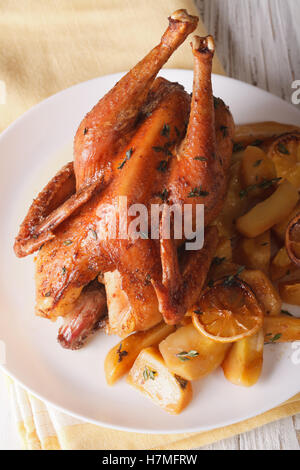 Whole baked chicken with lemon and thyme close-up on a plate. vertical view from above - Stock Photo