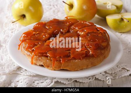 Apple pie Tarte Tatin with caramel close-up on a plate. horizontal - Stock Photo