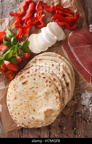 Italian freshly baked piadina with ingredients close-up on the table. vertical view from above - Stock Photo