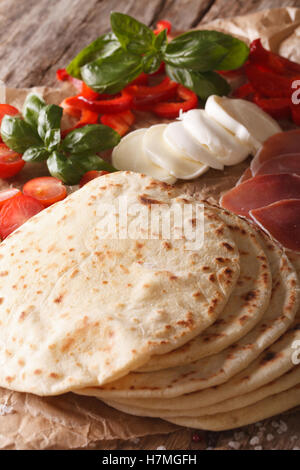 Freshly baked Italian piadina with the ingredients for the stuffing on the table macro. Vertical - Stock Photo