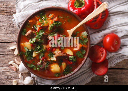 Traditional Hungarian goulash soup bogracs close-up in a bowl on the table. horizontal view from above - Stock Photo