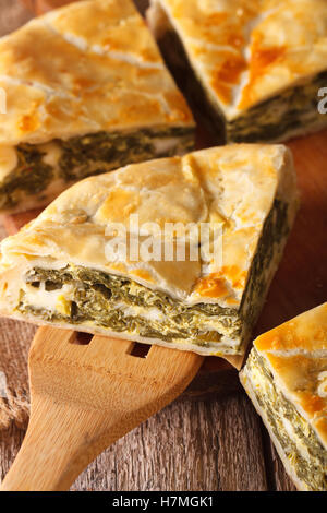 Greek pie with spinach and cheese spanakopita close-up on a table. Vertical - Stock Photo