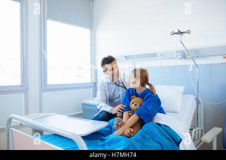 Doctor examining girl patient in hospital - Stock Photo