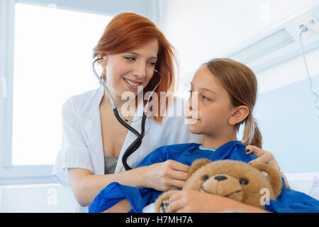 Doctor examining a young girl in hospital - Stock Photo