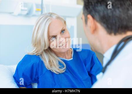 Doctor examining senior patient in hospital - Stock Photo