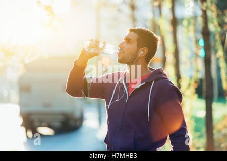 runner drinking mineral water at the break after running - Stock Photo