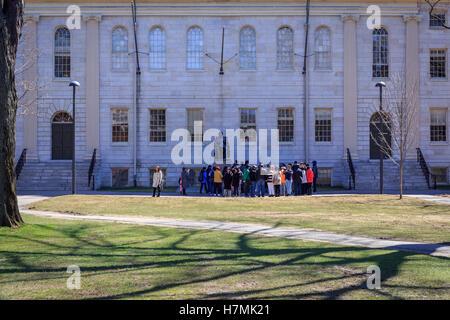 Tourist group gathered around the John Harvard statue in Harvard Yard, Cambridge, MA, USA. - Stock Photo