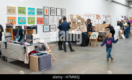 Young boy walking around designer stalls at the Renegade Craft Fair, an indoor indie designer market annual event - Stock Photo