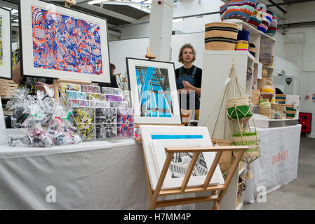 Young designer behind a stall selling prints and crafts at the Renegade Craft Fair an indoor indie designer market - Stock Photo