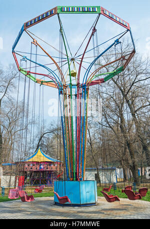Old children's carousel by chains in abandoned park in early spring - Stock Photo