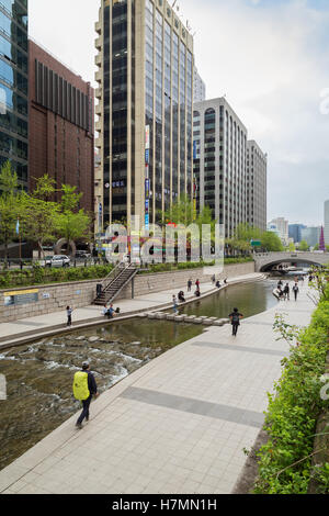 View of modern office buildings and people along the Cheonggyecheon Stream in Seoul, South Korea. - Stock Photo