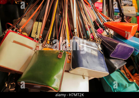 Colourful handbags for sale on market in Covent Garden in London - Stock Photo
