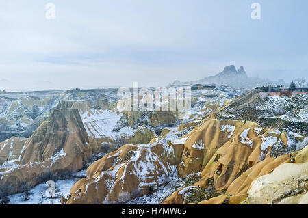 The amazing landscape of the Pigeon Valley covered with snow and the misty Uchisar rock on the background, Cappadocia, - Stock Photo