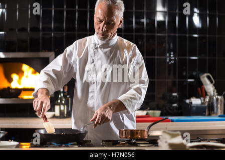 Serious chef mixing mushrooms on the frying pan - Stock Photo