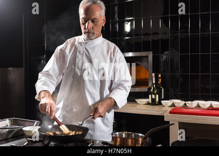 Involved chef mixing mushrooms on the frying pan - Stock Photo