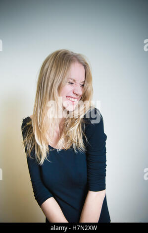 Young blonde woman, smirking with little grimace on white background - Stock Photo