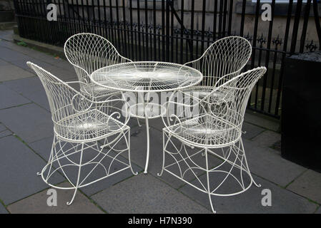 white wrought iron table and chairs on patio with a border