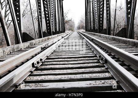 close up of  steel and wood train tracks on man made train or locomotive bridge over river - Stock Photo