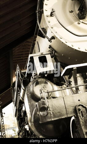 close up of historical steam locomotive engine parked in an old railway station - Stock Photo