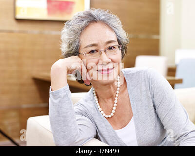 portrait of a senior asian woman, sitting on couch looking at camera smiling - Stock Photo