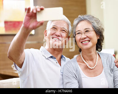 senior asian couple taking a selfie at home using cellphone - Stock Photo