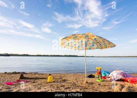 Parasol on the river bank, under which the scattered items and toys - Stock Photo