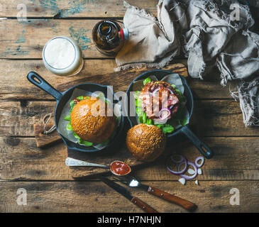 Homemade beef burgers with crispy bacon, lettuce and onion rings - Stock Photo